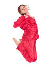 Jumping smiling young woman in red pajamas Stock Images
