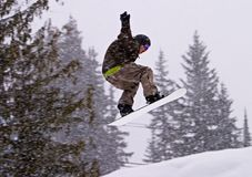 Jumping With A Snowboard. A man on a snowboard performing a jump. The arms are windmilling to stay in balance. It was snowing heavily and the snowflakes are royalty free stock photos