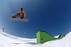 Jumping snowboarder. Snowboarder jumping over an obstacle on a sunny day with blue sky on a slope in the mountains royalty free stock images