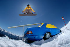 Jumping snowboarder. Snowboarder jumping over a car on a sunny day with blue sky on a slope in the mountains Royalty Free Stock Photo