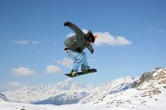 Jumping Snowboarder. Snowboarder jumping with mountains and sky in the background Royalty Free Stock Image
