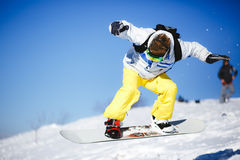 Jumping snowboarder on blue sky background Stock Image
