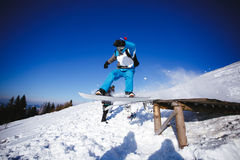 Jumping snowboarder on blue sky background Royalty Free Stock Image