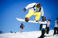 Jumping snowboarder on blue sky background Stock Images