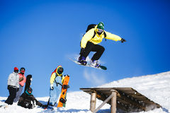 Jumping snowboarder on blue sky background Stock Photos