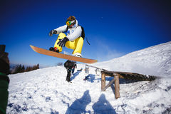 Jumping snowboarder on blue sky background Stock Photography