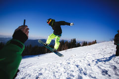 Jumping snowboarder on blue sky background Royalty Free Stock Photos