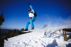 Jumping snowboarder on blue sky background Royalty Free Stock Photo