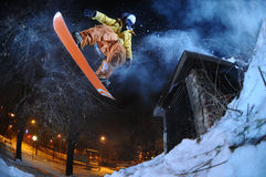 Jumping snowboarder in the city in winter Stock Image