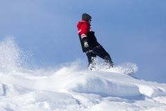 Jumping snowboarder from hill in winter. In the park in nature Royalty Free Stock Photos