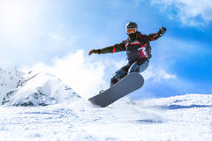 Jumping snowboarder from hill in winter Stock Image