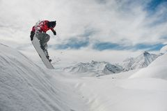 Free Jumping Snowboarder Keeping His Hand On The Snowboard On The Background Of Mountains And Sky Royalty Free Stock Images - 127630549