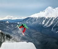 Snowboarder in mountain. Jumping snowboarder keeps one hand on snowboard in mountains in ski resort on blue sky background Royalty Free Stock Images
