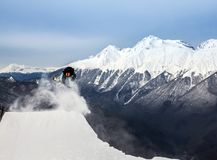 Snowboarder in mountain. Jumping snowboarder keeps one hand on snowboard in mountains in ski resort on blue sky background Stock Images