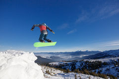 Jumping snowboarder in mountains in ski resort on blue sky background Dragobrat Stock Images