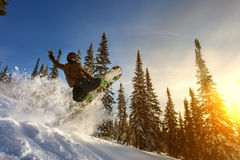 Jumping snowboarder on snowboard in mountains in ski resort. On blue sky background Royalty Free Stock Photos