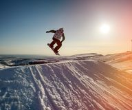 Jumping snowboarder in mountains Stock Photo