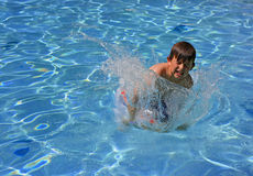 Jumping, splashing in a pool stock image