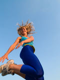 Jumping sporty girl. Beautiful fit blond girl jumping smiling cheerful Royalty Free Stock Images