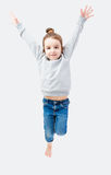 Jumping sporty little girl. Child in a gray sweatshirt and jeans. Gray background. Set of other clothing for children and adults in my portfolio Stock Photos