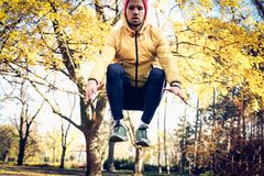 Jumping squats in nature. Man working. Sporty man in park Royalty Free Stock Photography