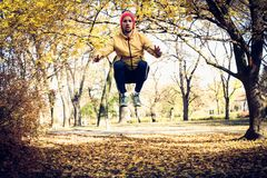 Jumping squats in nature. Young man exercise. Autumn season. Jumping squats in nature. Young man exercise. Autumn season in park Royalty Free Stock Images