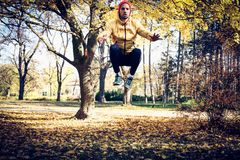 Jumping squats in nature. Young man exercise. Jumping squats in nature. Young man exercise in park. Autumn season Stock Photo