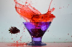 A jumping strawberry. Strawberries jumping into the blue cup. Water explosion Stock Photography
