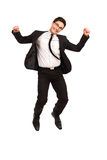 Jumping student. Jumping young man in black suit. Full length studio shot isolated on white Stock Image