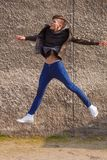 Brunet. Jumping stylish young brunet in leather jacket Stock Photography