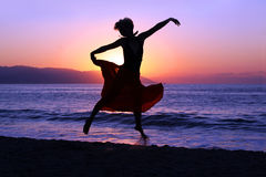 Jumping at sunset. Dramatic image of a woman dancing by the ocean at sunset Stock Image