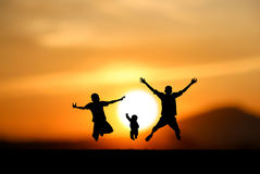 Jumping at sunset. Silhouette of  boys jumping with joy at sunset Stock Photo