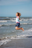 Jumping the Surf. Young girl jumps the surf at a beach Stock Image