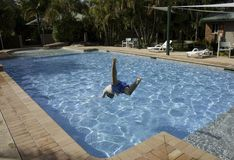 Jumping into swimming pool. Teenage boy jumping into a swimming pool in summer Stock Photo