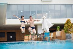 Jumping into swimming pool. Young Vietnamese couple jumping into the swimming pool Royalty Free Stock Photography