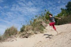 Jumping teenager. Teenager playing at the seaside, running down dunes Stock Image
