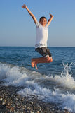 Jumping teenager boy on stone seacoast Royalty Free Stock Photography