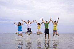 Jumping teens. Young people jumping on the beach Stock Photos