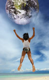 Jumping to the planet on beach Stock Photography