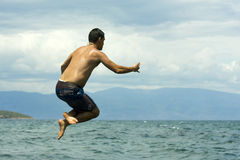 Jumping to sea. A young cute man is jumping to sea Royalty Free Stock Image