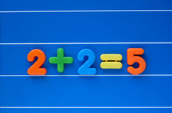 Jumping to the wrong conclusion. The classic putting two and two together and getting five, created from a child's toy number set. Sum placed in centre of image Royalty Free Stock Image