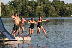 Jumping  Family. Family jumps together off raft into lake Royalty Free Stock Photography