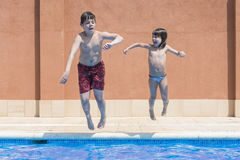 Jumping together to pool Royalty Free Stock Image