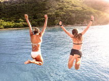 Jumping from the top deck of a floating Bar. Two teens jumping from the top deck of a floating bar in the virgin islands Stock Photography