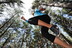 Jumping trail runner. Trail running jump fitness woman training alone outdoors in the forest Stock Photography