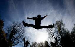 Jumping on trampoline in blue sky Stock Image