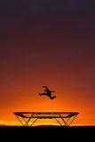 Jumping on trampoline in sunset Stock Photography