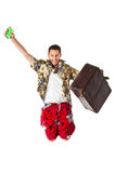 Jumping traveller. A young, attractive male in a colorful outfit ready to travel as a stereotype tourist Royalty Free Stock Photo