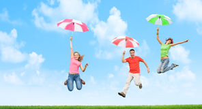 Jumping with umbrellas Royalty Free Stock Photo