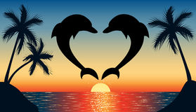 Jumping up dolphin shaped heart with sunset. Silhouette of two dolphins jumping out of water in the ocean shaped heart and silhouette of palm tree at sunset Stock Image